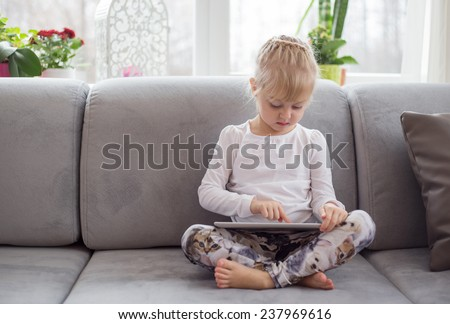 Young girl sitting on couch and using tablet computer - stock photo