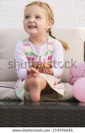 Young girl sitting on couch smiling