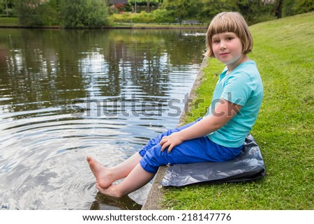 Young girl sitting on grass with bare feet in water from pond