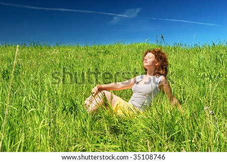 Young girl sitting on green field