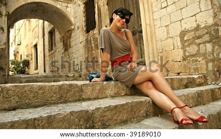 Young girl sitting on stairs in a old town - stock photo