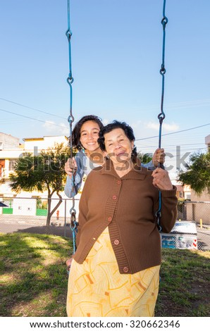 Young girl sitting on swing with grandmother in front, happily posing for camera. - stock photo