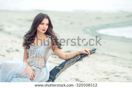 Young girl sitting on the beach after sunset in the sea background. Fashion model woman. Magic, fantasy, dreaming, summer girl, beauty, art portrait. Beautiful girl. Woman wearing long chiffon dress. - stock photo