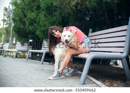 Young girl sitting on the bench and playing with her white husky dog. - stock photo