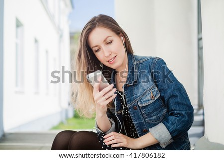 Young girl sitting on the college campus yard listening to the music on the smartphone