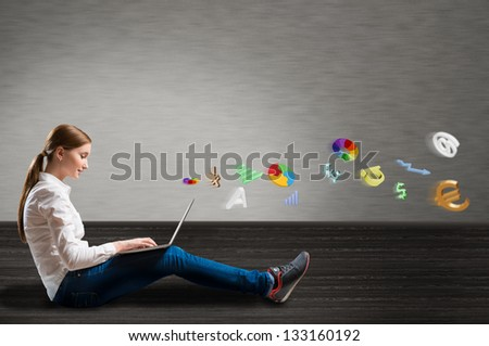 young girl sitting on the floor with a laptop from which emerge the signs and symbols - stock photo