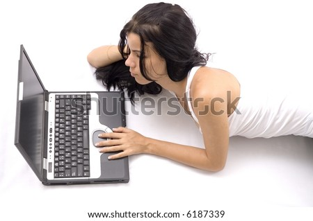 Young girl sitting on the floor with opened laptop - isolated over white