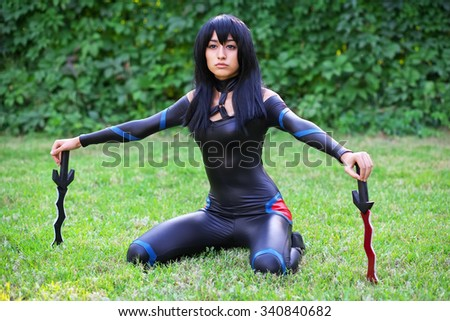 Young girl sitting on the grass and holding two dirks. Original cosplay character - stock photo