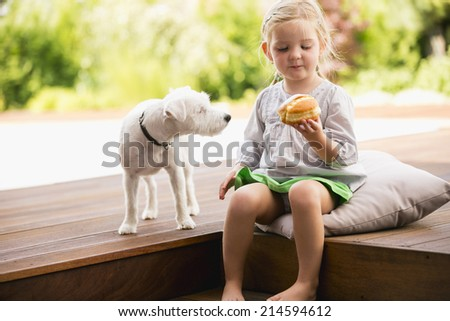 Young girl sitting on wooden steps with her dog eating doughnut - stock photo