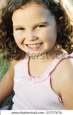 Young girl sitting outdoors smiling - stock photo