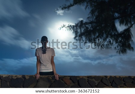 Young girl sitting watching the full mood light up the sky. (Taken with long exposure) - stock photo