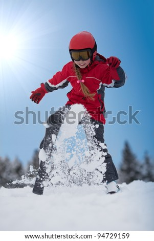 Young girl skier throws up snow with her ski