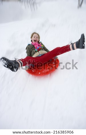 Young girl sledding down snow slope - stock photo