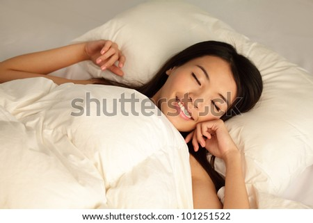 Young girl sleep peaceful with smile on home bed at night , model is a asian woman - stock photo