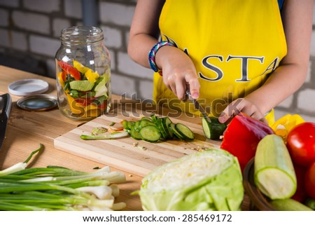 Young girl slicing a cucumber for bottling with assorted bell peppers, cabbage and tomatoes, close up of her hands