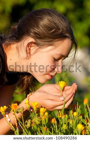 Young girl smelling yellow flower in garden - stock photo