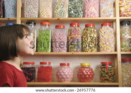 young girl smiling at camera in sweet shop