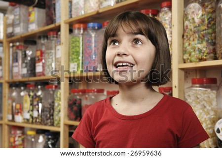 young girl smiling in awe at rows of sweets
