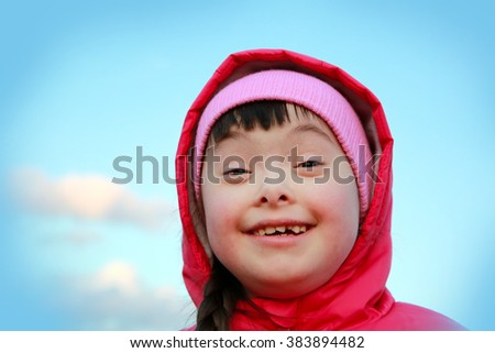 Young girl smiling on background of the blue sky - stock photo