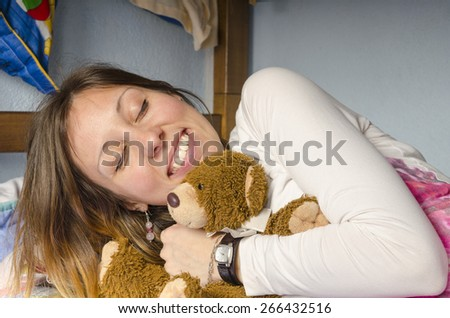 Young girl smiling while hugging her bear on the bed - stock photo