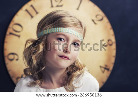 Young girl smiling with a large vintage clock behind her