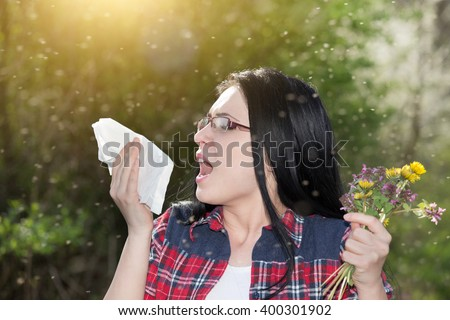 Young girl sneezing and holding paper tissue in one hand and flower bouquet in other. Allergies concept - stock photo