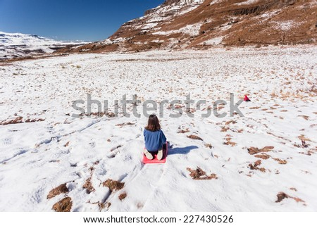 Young Girl Snow Playtime Young girl having playtime fun with snow ski  board on shallow slopes in mountains - stock photo