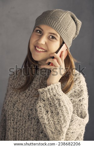Young girl speaking to a smartphone and smiling. Dressed casual - stock photo