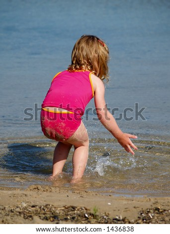 young girl splashing water at the beach