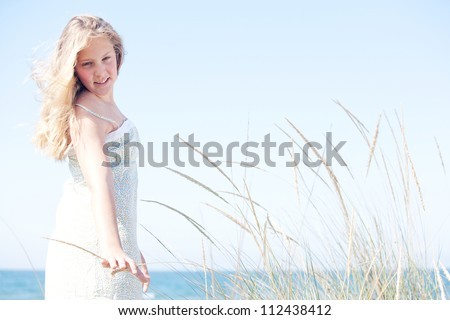 Young girl standing against a blue sky with long grass by the sea, turning and touching the grass. - stock photo