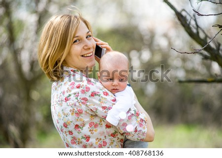 young girl standing in a lush garden with a small baby and talking on the phone