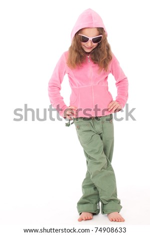 Young girl standing in pink top and green trouser pants and hood and sunglasses looking down with hands on hips - stock photo