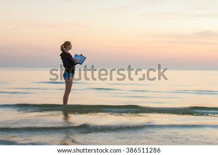 Young girl standing in the water on the beach, and draws on the colors of the landscape with sunset on a piece of paper