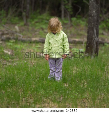 Young girl standing in the woods looking down,