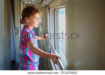Young girl standing inside train and pensively looking out window