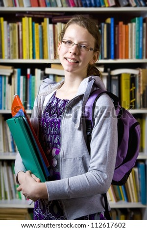 Young girl standing near the bookshelf - stock photo