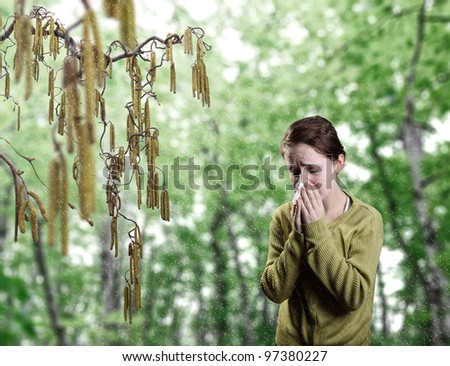Young girl standing next to catkins blowing her nose - stock photo