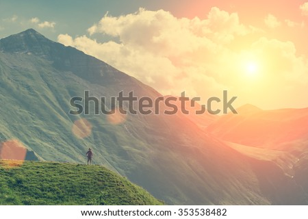 Young girl standing on the top up against the sky and mountain  - stock photo