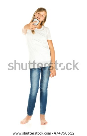Young girl standing taking a selfie with her mobile phone over white background
