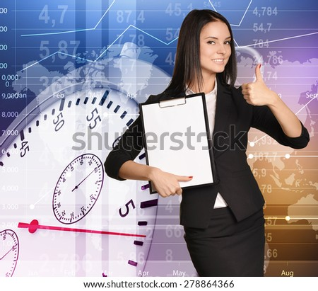 Young girl stands on background stopwatch holding clipboard and showing sign thumb up.