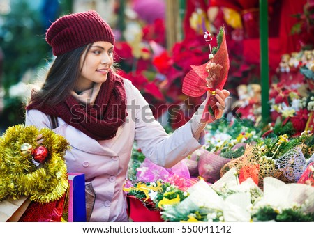 Young girl staying near a counter with mistletoe at Xmas fair