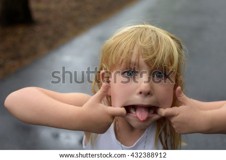 young girl sticking tongue out making silly face - stock photo