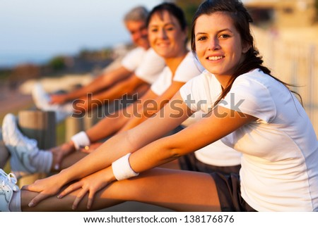 young girl stretching her leg two warm up before exercise at the beach - stock photo