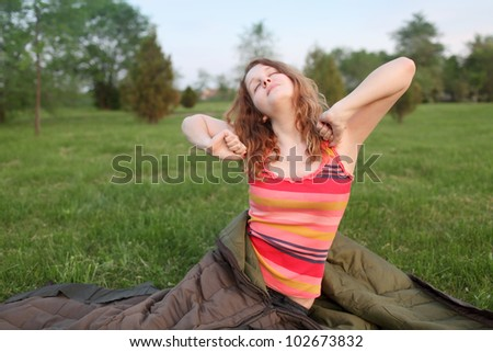 Young girl stretching  in early morning at meadow