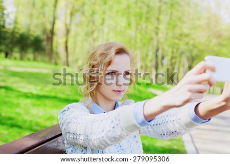 young girl student having fun and taking selfie photo on smartphone camera outdoor in green park in sunny day, teenage trand, people concept