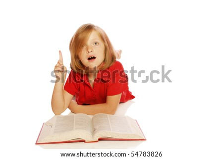 Young girl studying a book looking surprised - stock photo