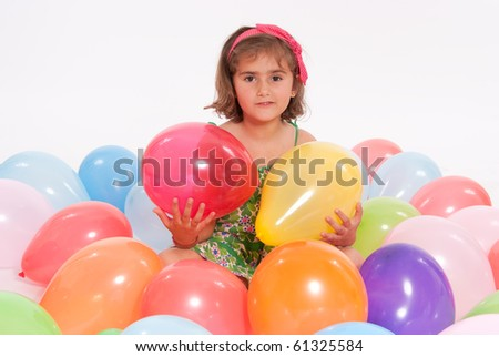 Young girl surrounded by colourful balloons - stock photo