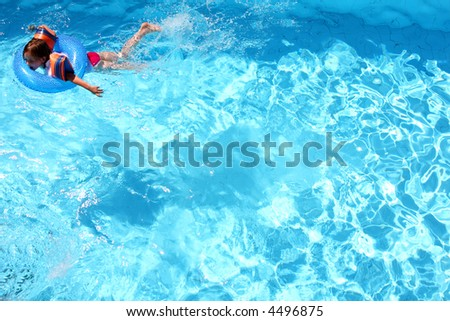 Young girl swimming in a pool all on her own