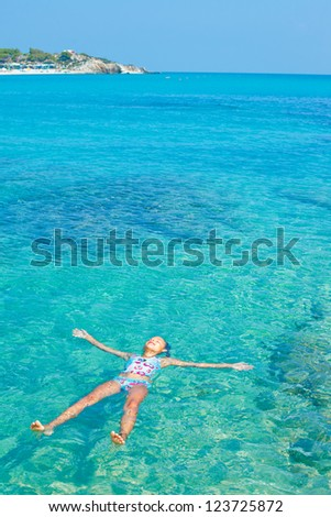 Young girl swimming in the transparent sea. Vertical view