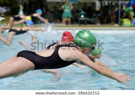 Young girl swims in swimming gala race competition